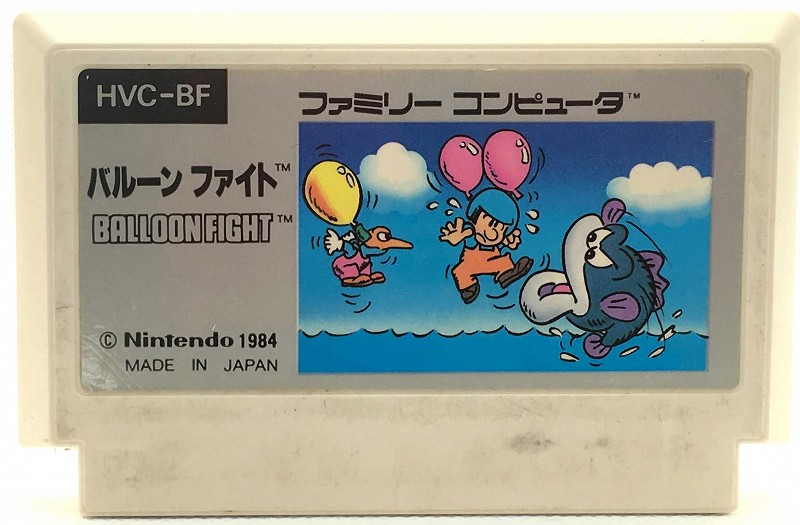 Photo of Balloon Fight for the Nintendo Famicom. White cartridge with a few dark blemishes and scratches on it.